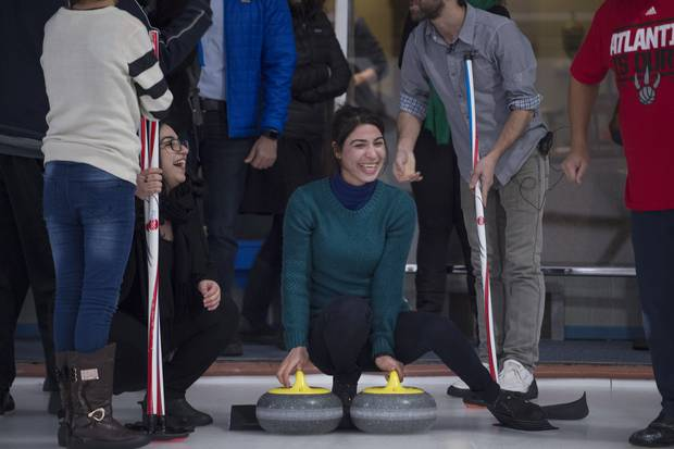 A Yazidi refugee from Kurdistan (centre) is all smiles during an outing to the Royal Canadian Curling Club on Mar 15 2017.