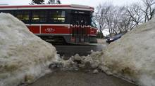 An eastbound streetcar on Dundas Street West passes a pile of snow shovelled near the street on Feb. 11 2013. (Fred Lum/The Globe and Mail)