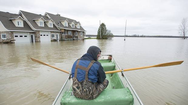 François Lussier rows a small boat along a flooded street in the town of Rigaud, Que., west of Montreal, on May 8, 2017.