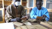 Two archivists, Aboubakar Yaro (left) and Alphamoye Djeite (right), study ancient manuscripts in a library in the Malian town of Djenne. (Yaro is wearing a mask to protect him from dust.) They are cataloguing the manuscripts as part of a British Library project to digitize copies of 200,000 manuscript pages in Djenne. Similar manuscripts in Timbuktu are under serious threat because Mali's north has been captured by Islamist militants who have already destroyed some of Timbuktu's cultural treasures. (Geoffrey York/The Globe and Mail)