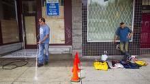 A caretaker power washes the sidewalk in front of a newly renovated building on East Hastings near vendor in the DTES in Vancouver on Wednesday. (Ben Nelms/The Globe and Mail)