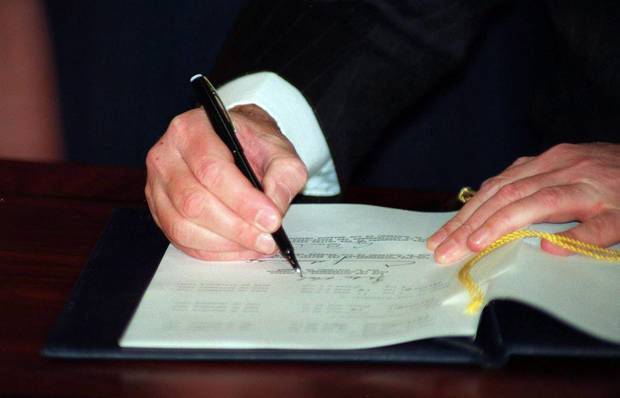 Prime Minister Brian Mulroney signs the North American Free Trade Agreement during a signing ceremony in Ottawa, Dec.17, 1992.