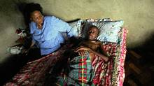 A health-care worker visits HIV sufferer Nkosinathi Mthembu at his home in Esikhawini township near Empangani in South Africa's Kwa-Zulu Natal province. South Africa has the world's largest number of AIDS cases, with more than five million people infected. (MIKE HUTCHINGS/REUTERS/MIKE HUTCHINGS/REUTERS)
