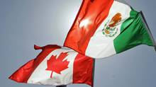 The flags of Canada and Mexico fly in the breeze at the Louis Armstrong International Airport in New Orleans ahead of a leaders summit on April 21, 2008. (Judi Bottoni/Associated Press)