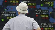 A man looks at a securities firm's electronic stock board in Tokyo Thursday, Aug. 16, 2012. (Shizuo Kambayashi/AP)
