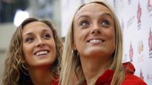 Marie-Pier Boudreau-Gagnon, right, and Elise Marcotte, Canadian Senior National Team and duet members, listen to a speaker at the unveiling of the Canadian synchronized swimming duet swimsuits for the 2012 Olympic Games during a news conference in Calgary, Alta., Saturday, May 12, 2012. (The Canadian Press)