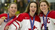Team Canada Meghan Agosta, goaltender Shannon Szabados and captain Hayley Wickenheiser, left to right, show off their gold medal after defeating Team USA in the gold medal final game at the World Women's Ice Hockey Championships Saturday, April 14, 2012 in Burlington, Vermont. THE CANADIAN PRESS/Paul Chiasson (Paul Chiasson/CP)