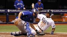 Tampa Bay Rays center fielder Desmond Jennings (8) slides safe into home place as Toronto Blue Jays catcher Josh Thole (22) attempted to tag him out during the fifth inning at Tropicana Field. (Kim Klement/USA Today Sports)