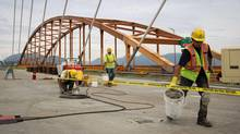 Workers fill holes on the new Port Mann Bridge as construction continues while the old bridge is pictured behind them in Surrey, B.C., on June 21, 2012. (DARRYL DYCK for The Globe and Mail)