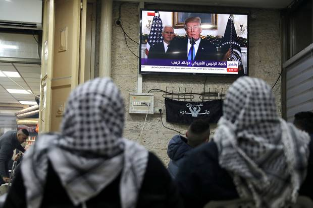Palestinians in Jerusalem's Old City watch a televised broadcast of U.S. President Donald Trump delivering an address on Dec. 6, 2017, where he announced that the United States recognizes Jerusalem as the capital of Israel.