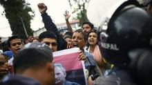 Anti-government protesters demanding the resignation of Nepal's Prime Minister Baburam Bhattarai, seen in photograph at center, shout slogans during a demonstration outside his residence in Katmandu, Nepal, July 18, 2012. (Niranjan Shrestha/AP)