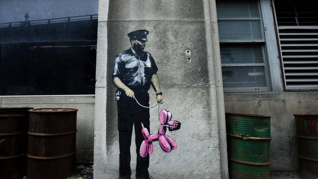 Graffiti from famed British graffiti artist Banksy is displayed on a wall in Toronto on Tuesday, May 11, 2010.