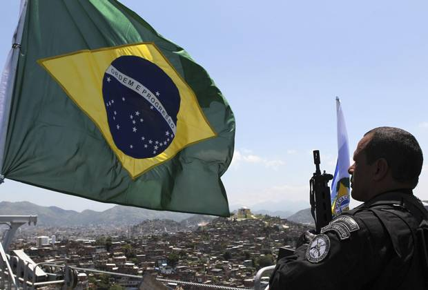 A policeman salutes the Brazilian national flag atop the Alemao hill after invading the slum in Rio de Janeiro on Nov. 28, 2010.
