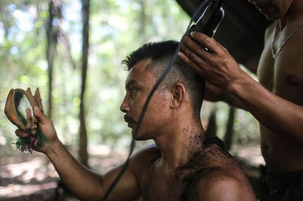 FARC rebel Cristobal, who has been in the guerrilla organization for 15 years, gets a haircut to prepare before watching the peace agreement signing ceremony.