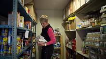 A volunteers at the Whistler food bank stocks the shelves with food for distribution to the needy December 10, 2012. (John Lehmann/The Globe and Mail)