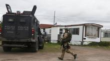 A Royal Canadian Mounted Police (RCMP) officer runs past the home, which according to local media was where Justin Bourque resided, in a trailer park in Moncton, New Brunswick June 5, 2014. (© Christinne Muschi / Reuters/REUTERS)