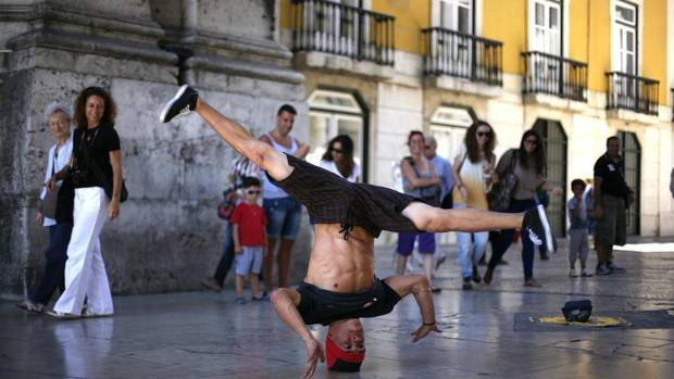 Alberto Perdomo, 22, dances during a street performance in downtown Lisbon Aug. 1, 2012. Mr. Perdomo is one of five hip hop dancers forced by lack of work to head out to the streets to support themselves. (RAFAEL MARCHANTE/REUTERS)