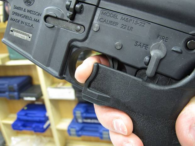 An employee of North Raleigh Guns demonstrates how a bump stock fits over a gun's trigger opening.