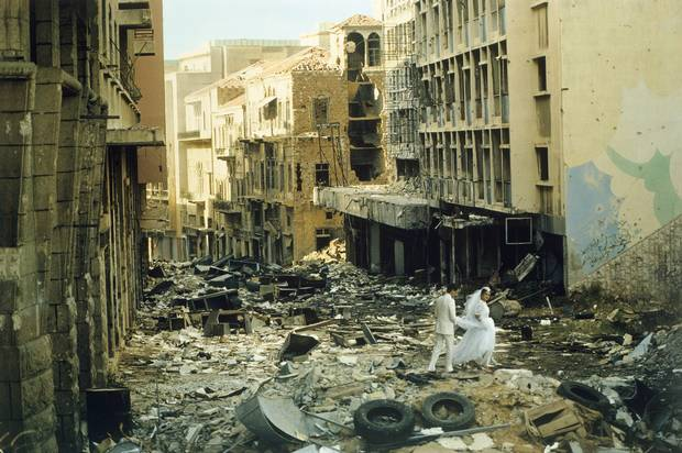 Just married, 23 years old Abed (Muslim groom) and 19 years old Arige (Christian bride) walk through the bombed ruins of Beirut, Lebanon, 1983.