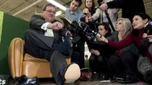 Finance Minister Jim Flaherty puts on his annual pre-budget shoes at the Roots leather factory in Toronto. (NATHAN DENETTE/THE CANADIAN PRESS)