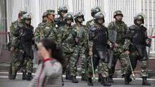Paramilitary policemen with shields and batons patrol near the People's Square in Urumqi, China's northwestern region of Xinjiang, Friday, May 23, 2014. A day after the attack in Xinjiang's capital of Urumqi, survivors told of their terror during the attack and said they no longer feel insulated from a long-simmering insurgency against Chinese rule, which has struck their city twice in recent weeks. While the perpetrators haven't been named, Chinese authorities have blamed recent attacks on radical separatists from the country's Muslim Uighur minority. (Andy Wong/AP)
