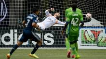 Vancouver Whitecaps' Sebastian Fernandez, left, of Uruguay, scores a goal against Seattle Sounders' goalkeeper Stefan Frei, centre, of Switzerland, as Zach Scott (obscured) and Micheal Azira, of Uganda, (42) watch during the first half of an MLS soccer game in Vancouver, B.C., on Saturday, July 5, 2014. (DARRYL DYCK/THE CANADIAN PRESS)