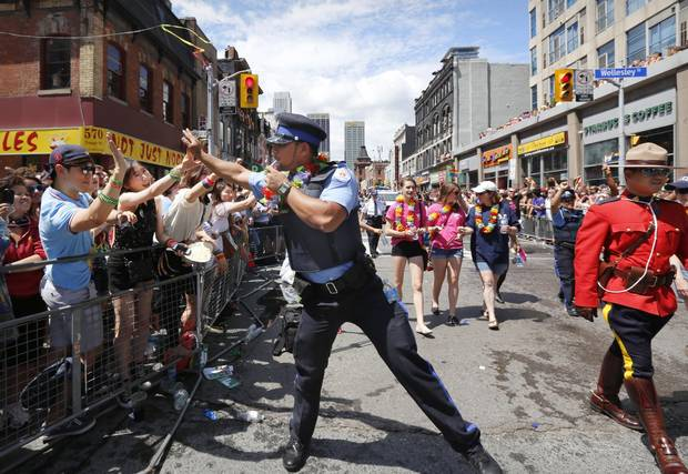 Police officer Keiss Zamir high-fives the crowd at the Toronto Pride Parade in Toronto on June 30, 2013.