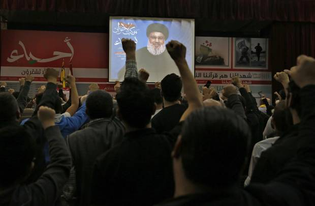 Hezbollah supporters raise their fists and cheer as they listen to a speech of Hezbollah leader Sheik Hassan Nasrallah, via a video link, during a rally marking Hezbollah Martyr's Day, in a southern suburb of Beirut, Lebanon, Friday, Nov. 10, 2017.