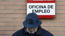 A man looks down as he waits in line to enter a government-run employment office in Madrid January 24, 2013. (SERGIO PEREZ/REUTERS)