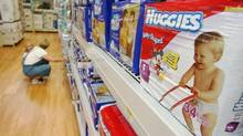 A shopper and her child look at diapers in Little Rock, Ark. in a file photo. Kimberly-Clark Corp. said Wednesday it will stop selling Huggies diapers in all European countries except Italy. (DANNY JOHNSTON/AP)