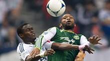 Vancouver Whitecaps' Gershon Koffie, left, of Ghana, and Portland Timbers' Franck Songo'o, of Cameroon, vie for the ball during the first half of an MLS soccer game in Vancouver, B.C., on Sunday October 21, 2012. (DARRYL DYCK/THE CANADIAN PRESS)