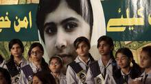 Pakistani students stand next to a portrait of Malala Yousufzai in Lahore on Nov. 10, 2012. (Mohsin Raza/Reuters)
