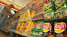 A convienent store customer make a purchase next to a shelf of Frito-Lay snacks. (LISA POOLE/Lisa Poole/AP)