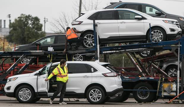 Workers at the Oakville Ford plant load cars onto a truck for shipment.