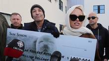 "actress Pamela Anderson and Sam Simon (left), producer of ""The Simpsons, "" talk to media outside the Canadian Sealers Association in St. John's, N.L., Tuesday, Dec.17, 2013. They attempted to deliver a letter with a million-dollar cheque to end the annual commercial seal hunt to the association but the office remained closed. (Paul Daly/CP)"