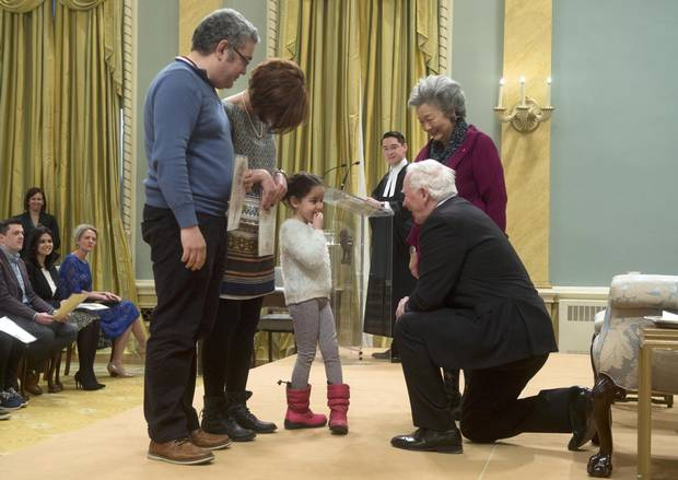 Former governor-general Adrienne Clarkson, right, Razik Mammeri, left, and Fairouz Djafri look on as Governor-General David Johnston kneels to speak with Yasmine Mammeri after presenting them with Canadian citizenship certificates at Rideau Hall on Jan. 31, 2017.