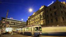 Trams drive past the offices of Swiss banks UBS, left, and Credit Suisse at Paradeplatz square in Zurich. At the end of 2007, UBS probably had the highest leverage ratio of any major bank in the world, with assets amounting to 53 times equity. (Arnd Wiegmann/REUTERS)