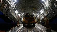 A French military armoured personnel carrier is loaded on to a British Royal Air Force C-17 aircraft at Evreux in northern France on Jan. 14, 2013. Canada is also providing support for the French mission to Mali, giving them use of a C-17 Globemaster for one week. (ANDREW WINNING/REUTERS)