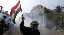 "A protester waves an Egyptian flag amidst clashes in Tahrir, Cairo November 25, 2012. Egyptian President Mohamed Mursi's decree that put his decisions above legal challenge until a new parliament was elected caused fury amongst his opponents on Friday who accused him of being the new Hosni Mubarak and hijacking the revolution. Police fired tear gas in a street leading to Cairo's Tahrir Square, heart of the 2011 anti-Mubarak uprising, where thousands demanded Mursi quit and accused him of launching a ""coup"". There were violent protests in Alexandria, Port Said and Suez. (Mohamed Abd El Ghany/Reuters)"
