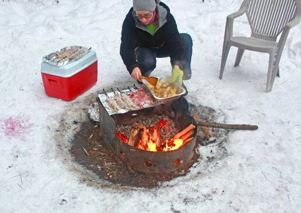Olga Kudinova cooks on an open fire, making a feast of lamb chops, kebobs and potatoes.