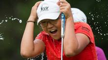Fifteen-year-old Lydia Ko, of New Zealand, is doused with water by her fellow golfers after winning the CN Canadian Women's Open LPGA golf tournament on Sunday. (DARRYL DYCK/The Canadian Press)