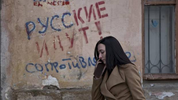 "A woman passes by a graffiti that reads ""The Russians are coming - Resistance"" in Simferopol, Ukraine, Friday, March 7, 2014. (Vadim Ghirda/AP)"