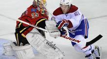 Montreal Canadiens' David Desharnais, right, is slowed down by the stick of Calgary Flames goalie Joey MacDonald during first period NHL action in Calgary, Alta., Wednesday, October 9, 2013. (LARRY MACDOUGAL/THE CANADIAN PRESS)