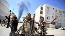 Libyan rebel fighters react as they search for snipers while fighting for the final push to flush out Moammar Gadhafi's forces in Abu Slim area in Tripoli August 25, 2011. (ZOHRA BENSEMRA/REUTERS/ZOHRA BENSEMRA/REUTERS)