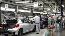 Employees work on the assembly line at the PSA Peugeot Citroen plant in Poissy, near Paris, in this file photo. Government aid for the ailing car maker would come with strings attached. (BENOIT TESSIER/REUTERS)