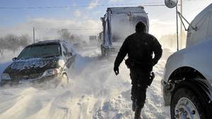 A Sarnia police officer checks on stranded motorists on London Line, East of Sarnia, Ont., on Tuesday Dec. 14, 2010. Two military helicopters took to the air to try to help 300 people trapped in their vehicles by a snowstorm.