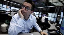 A trader reacts at his desk in front of the DAX board at the Frankfurt stock exchange. (ALEX DOMANSKI/REUTERS)