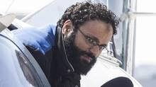 Chiheb Esseghaier, one of two men accused of plotting a terror attack on rail target, is led off a plane by an RCMP officer at Buttonville Airport north of Toronto on April 23, 2013. (CHRIS YOUNG/THE CANADIAN PRESS)
