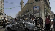 Palestinians gather around the wreckage of a vehicle following an Israeli airstrike in Gaza City, northern Gaza Strip, Monday, Aug. 25, 2014. (Adel Hana/AP)