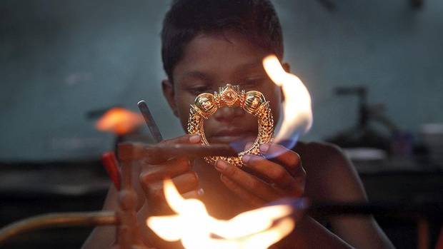 A goldsmith works on a gold bangle at a workshop in Kolkata in this file photo. India's passion for gold is putting such a strain on state finances that the government has raised the import tax from 4 per cent to 6 per cent. (RUPAK DE CHOWDHURI/REUTERS)